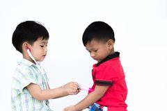Two litter boys is playing each other. Two litter boys is playing the plastic injection needle; one boy is the doctor and each boy is patient Stock Images
