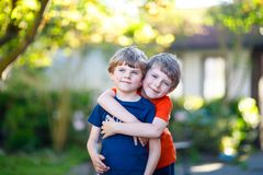 Two little active school kids boys, twins and siblings hugging on summer day Royalty Free Stock Images