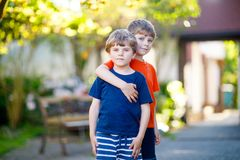 Two little active school kids boys, twins and siblings hugging on summer day Stock Photo