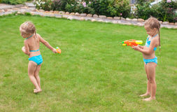 Two little adorable girls playing with water guns Stock Image