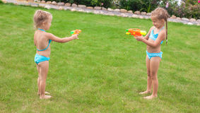 Two little adorable girls playing with water guns Royalty Free Stock Photography