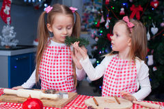 Two little adorable girls preparing gingerbread Royalty Free Stock Images