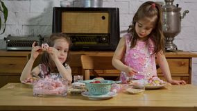 Two little adorable girls put on a cream and decorate delicious cupcakes. On a wooden table stock video