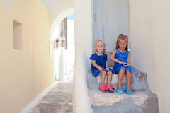 Two little adorable girls sitting on doorstep of Stock Photo