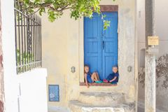 Two little adorable girls sitting on doorstep of Royalty Free Stock Photography
