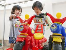 Two little Asian baby girls learning to wash their plastic big bikes stock images