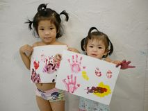 Two little Asian baby girls, sisters, enjoyed showing their artworks after making them by themselves - baby handprints stock photo