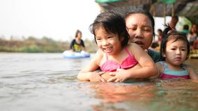 Two little Asian baby girls, sisters, enjoys playing water in a river with her auntie - playing outdoor and engaging with nature. Provides positive impact on stock video footage