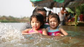 Two little Asian baby girls, sisters, enjoys playing water in a river with her auntie. Playing outdoor and engaging with nature provides positive impact on stock video