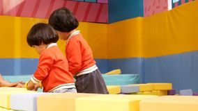 Two little baby girls, sisters, stacking up foam building bricks / blocks together at an indoor playground - playing foam blocks. Two little Asian baby girls stock footage