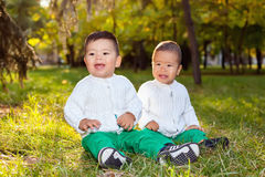 Two little Asian child playing in the Park, sitting on the grass Stock Image