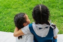 Two little asian girls sisters hugging happy post in school uniform, back to school concept royalty free stock photos