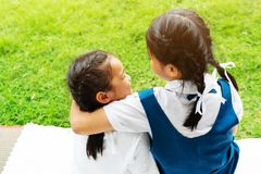Two little asian girls sisters hugging happy post in school uniform, back to school concept royalty free stock photo