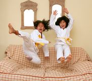 Two little asian judo gils jump on sofa royalty free stock photography