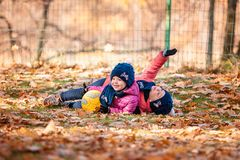 The two little baby girls playing in autumn leaves. The two little girls playing with ball in the autumn leaves in park Stock Photo