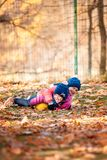 The two little baby girls playing in autumn leaves. The two little girls playing with ball in the autumn leaves in park Stock Photos