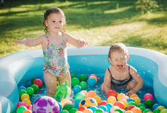 The two little baby girls playing with toys in inflatable pool in the summer sunny day Royalty Free Stock Image