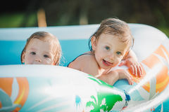 The two little baby girls playing with toys in inflatable pool in the summer sunny day Royalty Free Stock Images