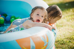 The two little baby girls playing with toys in inflatable pool in the summer sunny day Stock Photos