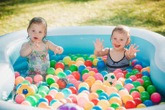 The two little baby girls playing with toys in inflatable pool in the summer sunny day Royalty Free Stock Photography