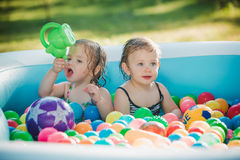 The two little baby girls playing with toys in inflatable pool in the summer sunny day Stock Photography