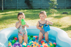 The two little baby girls playing with toys in inflatable pool in the summer sunny day Stock Image