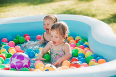The two little baby girls playing with toys in inflatable pool in the summer sunny day Royalty Free Stock Photo
