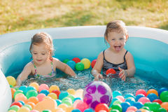The two little baby girls playing with toys in inflatable pool in the summer sunny day Royalty Free Stock Photos