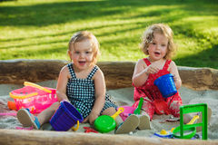 The two little baby girls playing toys in sand Royalty Free Stock Photography
