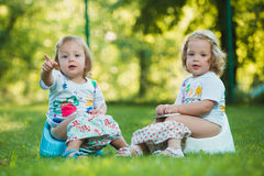 The two little baby girls sitting on pottys against green grass Stock Photo