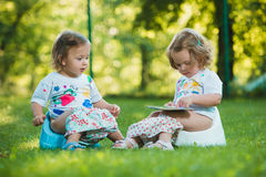 The two little baby girls sitting on pottys against green grass Stock Image