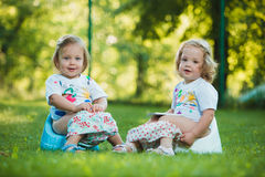 The two little baby girls sitting on pottys against green grass Stock Photos