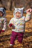 The two little baby girls standing in autumn leaves. The two little baby girls standing in the autumn leaves Stock Images