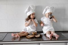 Two little baker girls are drinking tea with a pabcakes in the kitchen.  Stock Photography