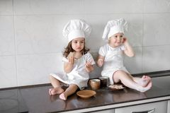 Two little baker girls are drinking tea with a pabcakes in the kitchen.  Royalty Free Stock Image
