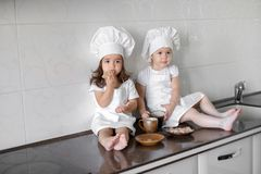 Two little baker girls are drinking tea with a pabcakes in the kitchen.  Royalty Free Stock Photos