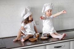 Two little baker girls are drinking tea with a pabcakes in the kitchen.  Stock Photo