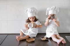 Two little baker girls are drinking tea with a pabcakes in the kitchen.  Royalty Free Stock Photo