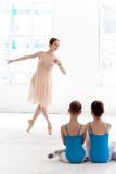 Two little ballerinas dancing with personal ballet teacher in dance studio Royalty Free Stock Photos