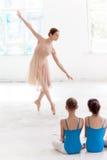 Two little ballerinas dancing with personal ballet teacher in dance studio Royalty Free Stock Photos