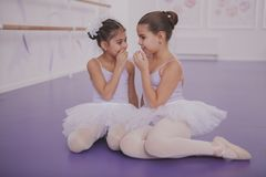Two little ballerinas talking after dancing lesson royalty free stock photography