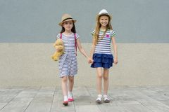 Two little beautiful girlfriends holding hands, girls walking in striped dresses, hats with backpack. Background gray wall stock photography