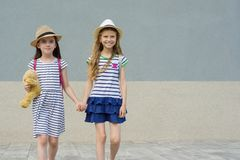 Two little beautiful girlfriends holding hands, girls walking in striped dresses, hats with backpack. Background gray wall, copy space stock photo