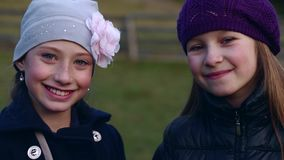 Two little beautiful girls look at the camera and smiling stock video footage