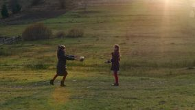 Two little beautiful girls playing with a ball on the nature at the sunset autumn. HD stock video footage