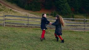 Two little beautiful girls whirl in nature, holding hands. In autumn evening stock video