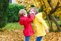 Two little best friends and kids boys autumn park in colorful cl. Othes. Happy siblings children having fun in red and yellow rain coats and rubber boots. Family Stock Images