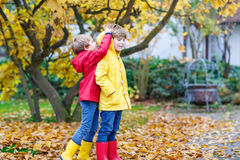 Two little best friends and kids boys autumn park in colorful cl. Othes. Happy siblings children having fun in red and yellow rain coats and rubber boots. Family Stock Image