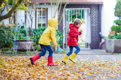 Two little best friends and kids boys autumn park in colorful cl. Othes. Happy siblings children having fun in red and yellow rain coats and rubber boots. Family Stock Photos