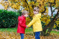 Two little best friends and kids boys autumn park in colorful cl. Othes. Happy siblings children having fun in red and yellow rain coats and rubber boots. Family Stock Photography